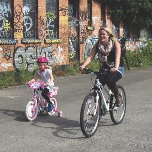 Girl on pink bike with stabilisers with Mum